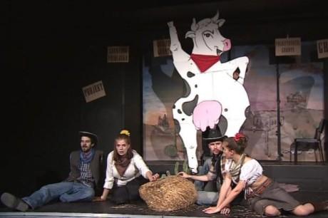 Čtvercovému pódiu vévodí kulisa velké stylizované krávy s vemenem v laškovném postoji panáčkujícího psa. FOTO archiv ČT