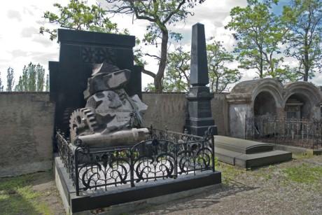 """Náhrobek Emila Škody se nachází severně od kostela v jeho těsné blízkosti, přiléhá k hřbitovní zdi. Náhrobek nechala v roce 1903 nainstalovat Škodova rodina, která dílo objednala od florentského sochaře Raffaela Romannelliho. Základem je """"skalisko"""" z růžové žuly, v přední části leštěné, jinde ponecháno s hrubým povrchem, z něhož vystupují hlaveň děla a ozubené kolo jako atribury Škodova podnikání. Na něm nápis tvořený bronzovými písmeny: """"EMIL RITTER VON SKODA / N / *19 N 1839 / M / + 8 AG 1900"""" (je zajímavé, že zkratky jsou v jazyku sochaře, tj. v italštině N - nato / narozen, M - morto / zemřel, N - novembre / listopad, AG - agosto / srpen). FOTO KAREL KOCOUREK"""