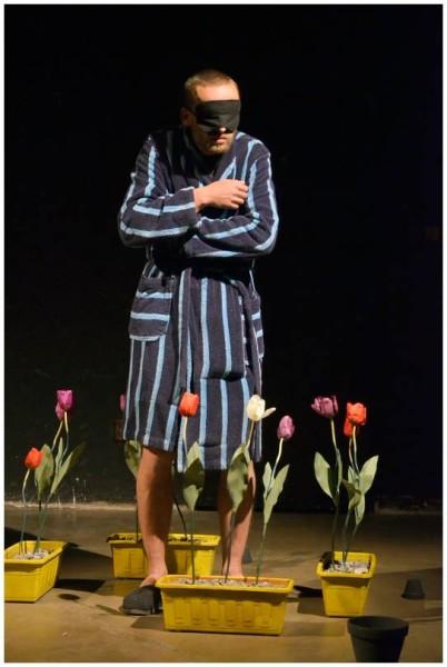 Zpěv poznenáhlu umlká, pokroucený básník v ohrádce z tulipánů ožívá. S klapkami na očích, halen tmou samoty. FOTO FB Divadla Krajiny