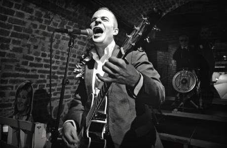 Bíle natřený, černě oděný herec Holenda, jediný bez rozšklebených úst, zato s dámským vlněním těla drnkl do kytary a zpíval: Jinak to nejde. FOTO archiv DHnP