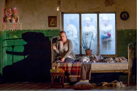 Jenůfa (Monika Mych-Nowicka) si na gauči stvořila svůj kout s uvadlou svatební myrtou, zamrzlými okny nahlížejí symbolické tanečnice FOTO MAGDALENA OŚKO