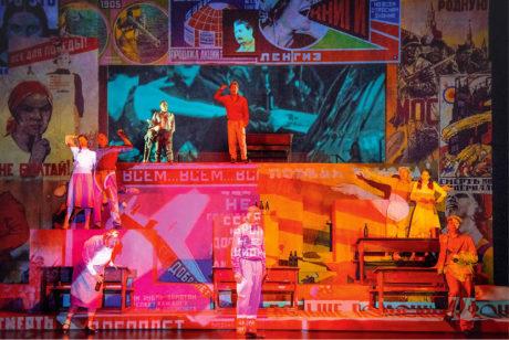 Na šedý podklad bloků a dveří se pomocí projekce vytváří koláž propagandistických plakátů... Nasza klasa, Národní divadlo v Oslu (režie Oskar Koršunovas) FOTO ARCHIV