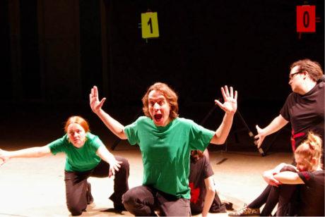 Z představení  Just!Impro. Martin Vasquez přihlíží výstupu kolegů Ládi Kardy (v červeném tričku) a Jiřího Axmana. Jeden improvizuje hlas, druhý pohyb postavy, kterou společně představují FOTO JUST!IMPRO